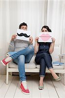 Couple sitting on sofa holding lips and moustache Stock Photo - Premium Royalty-Freenull, Code: 614-06442407