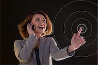 futuristic - Young woman on cellphone and touching virtual circle Stock Photo - Premium Royalty-Freenull, Code: 614-06442509