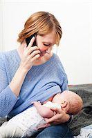 Mother on phone breast feeding newborn daughter Stock Photo - Premium Royalty-Freenull, Code: 614-06442514