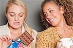 Woman staring at friend holding chocolate Stock Photo - Premium Royalty-Free, Artist: CulturaRM, Code: 614-06442629