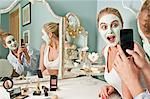 Woman wearing face mask being photographed by friend Stock Photo - Premium Royalty-Free, Artist: Cultura RM, Code: 614-06442643