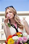 Young woman smelling rose from bouquet of flowers, eyes closed Stock Photo - Premium Royalty-Free, Artist: Ikon Images, Code: 614-06442748