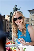Young woman having salad at restaurant outdoors Stock Photo - Premium Royalty-Freenull, Code: 614-06442758