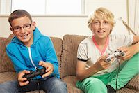 Two boys playing video game Stock Photo - Premium Royalty-Freenull, Code: 614-06442818