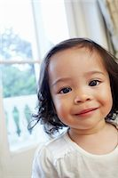 Portrait of a little girl smiling at camera Stock Photo - Premium Royalty-Freenull, Code: 614-0