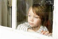 Little boy looking through window Stock Photo - Premium Royalty-Freenull, Code: 614-06442850