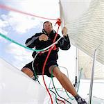 Man on yacht, pulling ropes Stock Photo - Premium Royalty-Free, Artist: Westend61, Code: 614-06442925