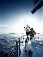 Couple steering a yacht Stock Photo - Premium Royalty-Freenull, Code: 614-06442933