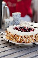 Fresh cake with berry fruit topping served in plate on wooden table Stock Photo - Premium Royalty-Freenull, Code: 698-06443724