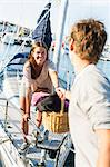 Happy young woman holding partner's hand while getting off from sailboat Stock Photo - Premium Royalty-Free, Artist: Robert Harding Images, Code: 698-06443741
