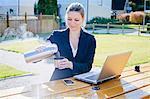 Mid adult businesswoman with laptop pouring hot tea in cup Stock Photo - Premium Royalty-Free, Artist: Blend Images, Code: 698-06443942