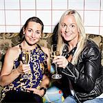 Portrait of happy female friends holding champagne flutes on sofa Stock Photo - Premium Royalty-Free, Artist: Blend Images, Code: 698-06443988