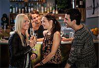 saloon - Bar tender looking at friends smiling at counter Stock Photo - Premium Royalty-Freenull, Code: 698-06443991