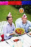 Happy men celebrating crayfish party in lawn