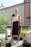 Portrait of happy young woman with gardening fork standing at urban garden Stock Photo - Premium Royalty-Free, Artist: Minden Pictures, Code: 698-06444200