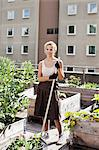 Young woman with gardening fork standing at urban garden Stock Photo - Premium Royalty-Free, Artist: Cultura RM, Code: 698-06444201