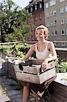 Happy young woman with wooden crate sitting at urban garden Stock Photo - Premium Royalty-Free, Artist: Blend Images, Code: 698-06444203