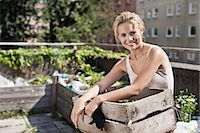 Portrait of happy young woman with wooden crate sitting at urban garden Stock Photo - Premium Royalty-Freenull, Code: 698-06444204
