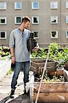 Young man with stacked flower pots standing at urban garden Stock Photo - Premium Royalty-Free, Artist: Blend Images, Code: 698-06444206