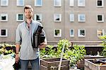 Portrait of young man with stacked flower pots standing at urban garden Stock Photo - Premium Royalty-Free, Artist: ableimages, Code: 698-06444207