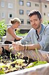 Portrait of young man gardening with woman at urban garden Stock Photo - Premium Royalty-Free, Artist: Cultura RM, Code: 698-06444216