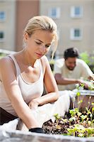 Young woman gardening at urban garden with man in the background Stock Photo - Premium Royalty-Freenull, Code: 698-06444219