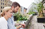 Side view of young Caucasian couple sitting at urban garden Stock Photo - Premium Royalty-Free, Artist: Blend Images, Code: 698-06444230