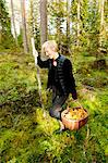 Happy young woman carrying basket full of mushrooms in forest Stock Photo - Premium Royalty-Free, Artist: Minden Pictures, Code: 698-06444308