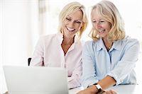 Happy businesswomen using laptop at desk in office Stock Photo - Premium Royalty-Freenull, Code: 698-06444404