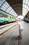 Young boy looking at something interesting on railroad platform Stock Photo - Premium Royalty-Free, Artist: Blend Images, Code: 698-06444437