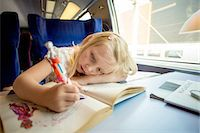Young girl drawing pictures while sitting on train's seat Stock Photo - Premium Royalty-Freenull, Code: 698-06444447