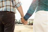Midsection of couple holding hands Stock Photo - Premium Royalty-Freenull, Code: 698-06444449