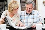 Happy couple reading newspaper at table Stock Photo - Premium Royalty-Free, Artist: Blend Images, Code: 698-06444470