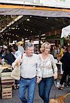Happy couple with dog walking against market