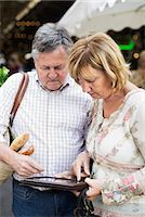 Couple using digital tablet with market in the background Stock Photo - Premium Royalty-Freenull, Code: 698-06444483