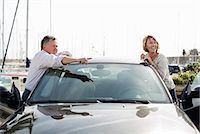 Senior man showing something to woman while leaning on car Stock Photo - Premium Royalty-Freenull, Code: 698-06444490
