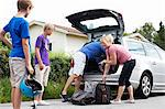 Happy Caucasian family loading luggage in car trunk for picnic Stock Photo - Premium Royalty-Free, Artist: Blend Images, Code: 698-06444498
