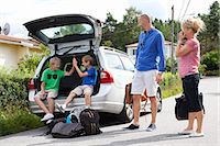 Caucasian couple looking at happy sons sitting in car trunk before going for picnic Stock Photo - Premium Royalty-Freenull, Code: 698-06444499