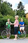 Portrait of happy mature woman with sons standing by bicycle on road Stock Photo - Premium Royalty-Free, Artist: CulturaRM, Code: 698-06444501