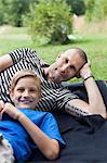 Portrait of mature man and son lying on grass at park Stock Photo - Premium Royalty-Free, Artist: Aflo Relax, Code: 698-06444512