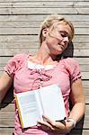 Directly above shot of mature woman with book relaxing on boardwalk Stock Photo - Premium Royalty-Free, Artist: Blend Images, Code: 698-06444518