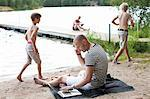 Mature man using laptop while communicating on cell phone at beach with family in the background Stock Photo - Premium Royalty-Freenull, Code: 698-06444527