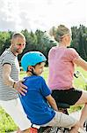 Man looking at son sitting behind woman on bicycle in park Stock Photo - Premium Royalty-Freenull, Code: 698-06444534