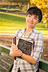 Outdoor Portrait of a Pretty Mixed Race Female Student Holding Books Looking Away. Stock Photo - Royalty-Free, Artist: Feverpitched                  , Code: 400-06457965