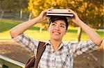 Portrait of a Pretty Mixed Race Young Female Holding Books on Her Head Outdoors at the Park on a Sunny Afternoon. Stock Photo - Royalty-Free, Artist: Feverpitched                  , Code: 400-06457968