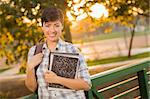 Outdoor Portrait of a Pretty Mixed Race Female Student Holding Books on a Sunny Afternoon. Stock Photo - Royalty-Free, Artist: Feverpitched                  , Code: 400-06457970