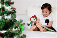 Young girl reading a book, Christmas tree in foreground Stock Photo - Premium Rights-Managednull, Code: 849-06466248
