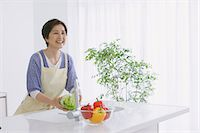 Senior adult woman washing vegetables in an open kitchen Stock Photo - Premium Rights-Managednull, Code: 859-06469748