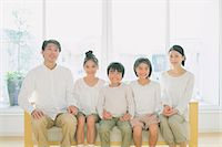 Family of five people holding hands while smiling at camera on the sofa Stock Photo - Premium Rights-Managednull, Code: 859-06469844