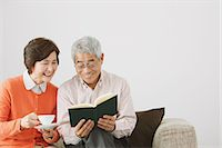 Senior adult couple having a coffee while reading a book on the sofa Stock Photo - Premium Rights-Managednull, Code: 859-06470191